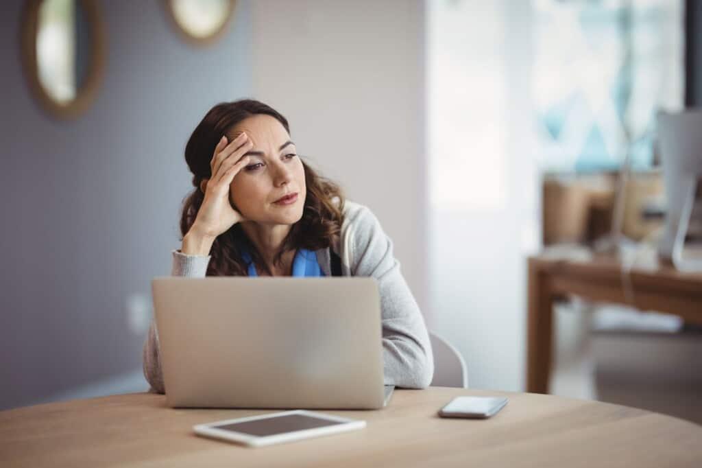 Mujer reflexiva con ordenador portátil